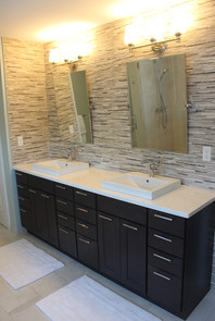 Berk Bathroom, designed by Patty Heath. Featuring dark contemporary cabinets with silver pulls, white marble countertops, and rough granite backsplash.