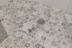 White Bathroom, Bow Street Apartment, designed by Ellen Lamoureaux. Close-up of hexagonal marble bathroom tiles on floor of the shower.