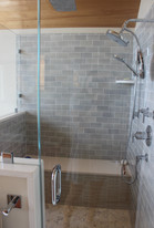 Master bathroom designed by Patty Heath, New Castle, NH. Featuring shower with glass tile, bench, rain shower head, power shower heads, and pebble grouted tiles.