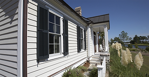Image of the front of a house with clappboard siding and shutters.