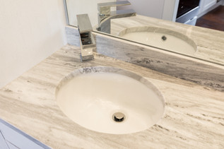 White Bathroom, Bow Street Apartment, designed by Ellen Lamoureaux. Close-up of bathroom countertop,  white quartz with a silver nickel sink fixture.