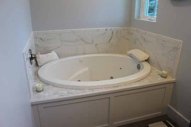 Bathroom designed by Nathan Johnson, featuring a jacuzzi tub with marble backsplash, hexagonal tile top, and grey cabinet cover.