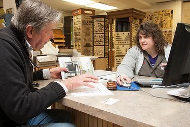 Image of Cramer's staff member assisting customer at counter.