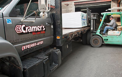 Image of fork-lift loading lumber onto Cramer's delivery truck.