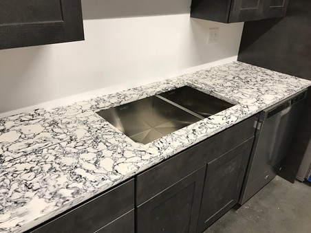 Dark washed transitional cabinets with a black and white marbled quartz countertop.