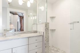 White Bathroom, Bow Street Apartment, designed by Ellen Lamoureaux. White-tiled glass shower, white bathroom vanity by Showplace Cabinets.