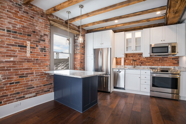 Bow Street Apartment Kitchen, Portsmouth NH Designer Ellen Lamoureaux. Featuring granite countertops, featuring stainless Steel G.E. appliances, and white Showplace kitchen countertops. Original Beams and Hardwood floors. A blue solitary kitchen island with a white granite countertop stands in the center.