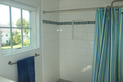 Guest bathroom designed by Nathan Johnson, featuring a multi-colored tile detailing on the shower, with porcelain tiles.