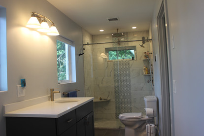 Bathroom designed by Nathan Johnson, featuring a glass shower, marble backsplash, and dark contemporary vanity.