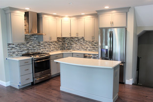 Lemieux Kitchen with glass tile backsplash, white cabinets, and white quartz countertop, designed by Nathan Johnson.