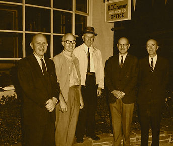 Image of R.C. Cramer and some of his sons in front of R.C. Cramer Lumber office sign.