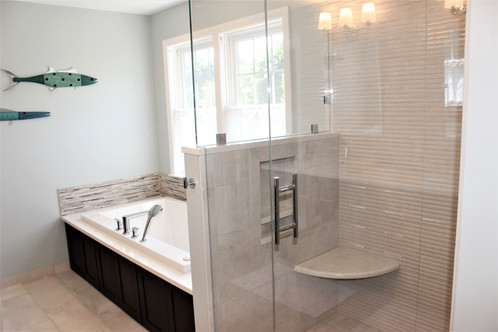 Berk Bathroom, designed by Patty Heath. Featuring a glass shower with stone floors and backsplash, and a jacuzzi tub, encased in dark wood cabinet paneling.