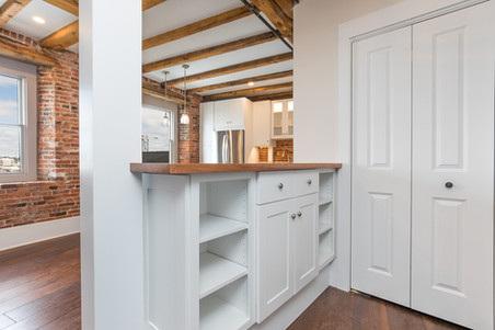 Bow Street Kitchen, Portsmouth NH Designer Ellen Lamoureaux.  Featuring granite countertops, featuring stainless Steel G.E. appliances, and white Showplace kitchen countertops. Original Beams and Hardwood floors.