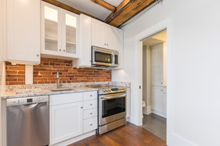 Bow Street Kitchen, Portsmouth NH. Designer Ellen Lamoureaux.  Featuring granite countertops, featuring stainless Steel G.E. appliances, and white Showplace kitchen countertops. Original Beams and Hardwood floors.