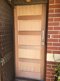 Unglazed entrance door with deadlock and pull handle.