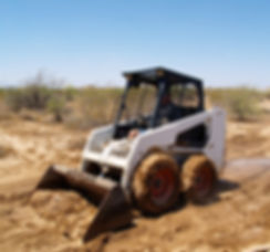 Construction worker driving a skid steer
