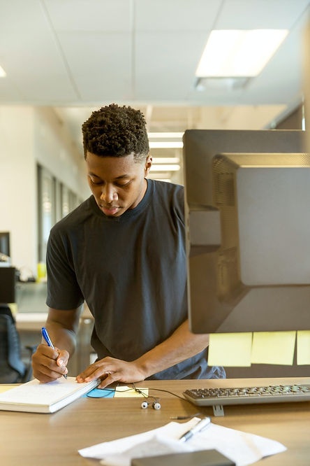 African American man taking notes in front of a computer