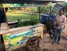 A Cambodian woman presents her vegetable cart to some members of the ASMC team
