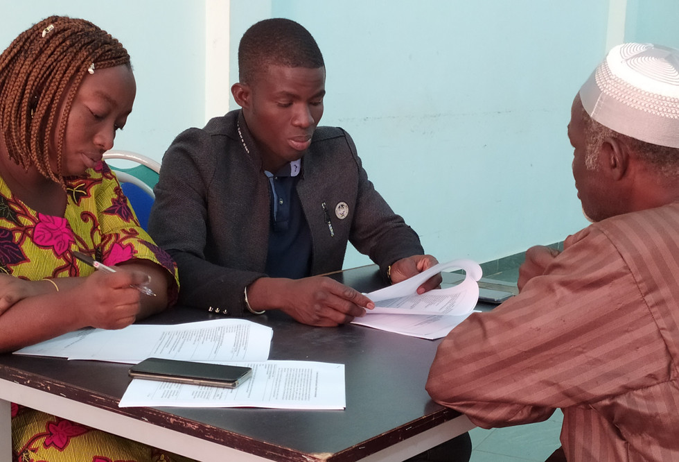 Two facilitators applying the Technology Readiness Assessment questionnaire to a household head who has used the planter, in Bobo-Dioulasso, Burkina Faso