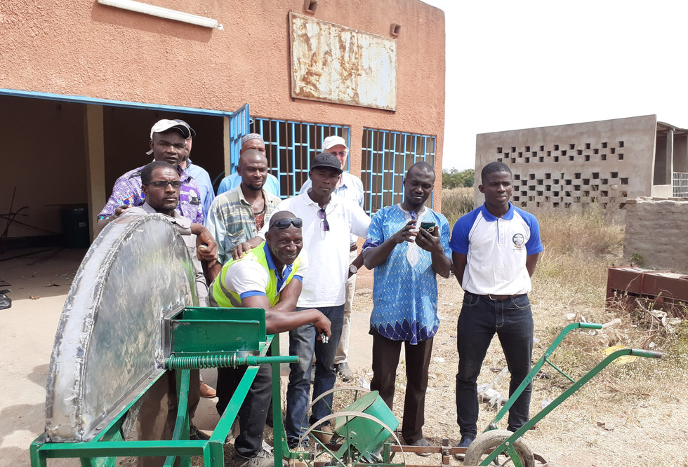 A group discusses adjustments to the ASMC prototype planter in Burkina Faso
