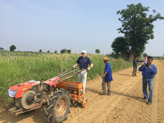 Former Director of ASMC, Dr. Alan Hansen demonstrates the two-wheel tractor drawn planter in Cambodia
