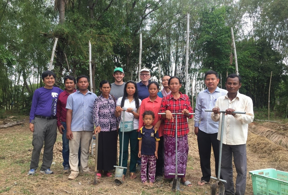 A group of Cambodian vegetable farmers pose for a photo with Dr. Alan Hansen and Timothy Rendall