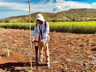 An intern takes a soil moisture reading in Cambodia.