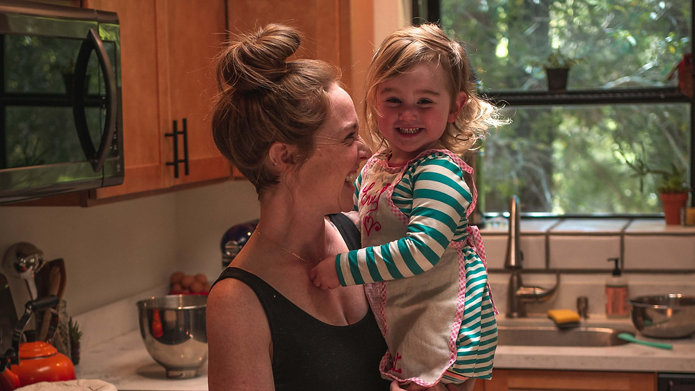 Smiling mother holding daughter in the kitchen