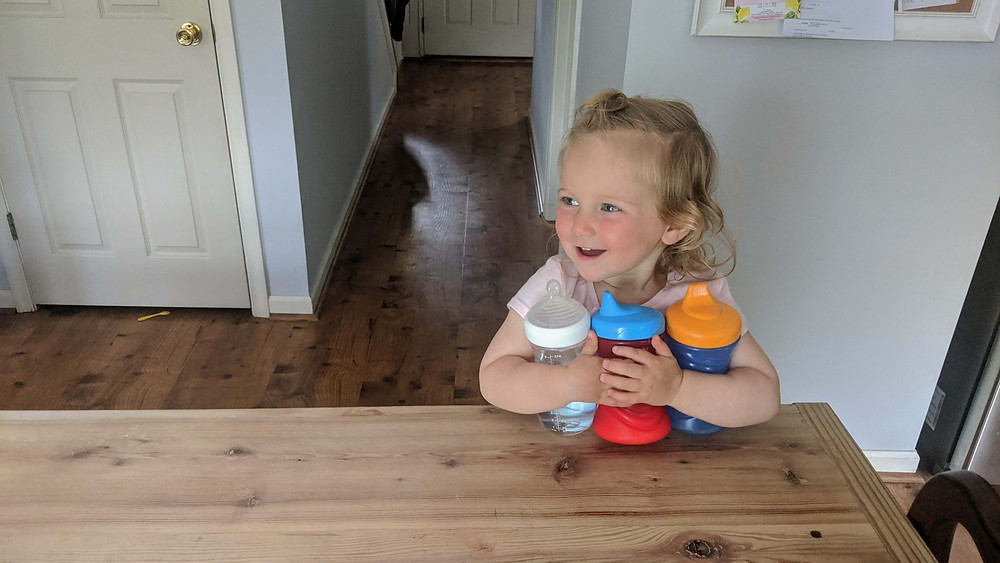 Toddler with three bottles sitting at the island in the kitchen