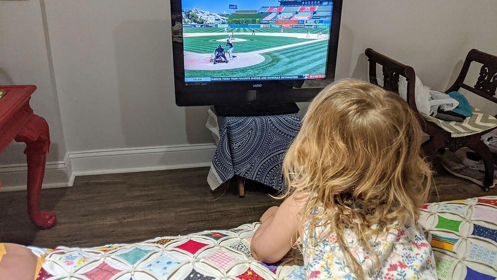 Toddler watching a baseball game on TV