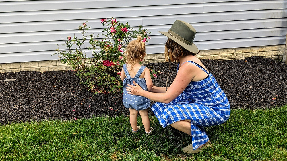 Mother and daughter looking at a rose bush