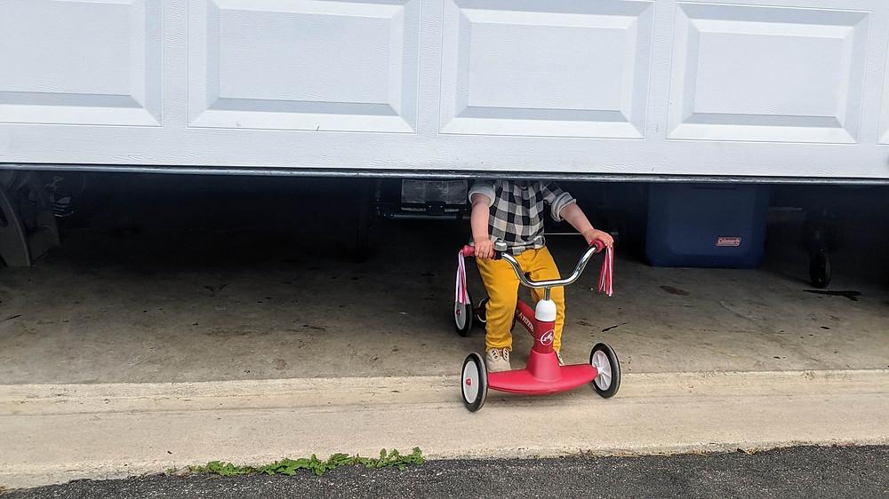Toddler stuck behind a half opened garage door