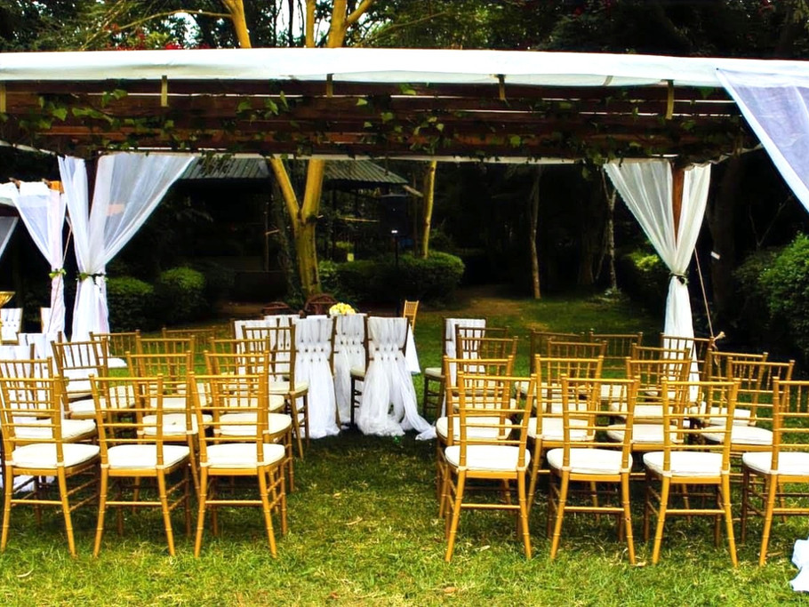 A wedding ceremony with pergola tent and chiavari chairs.