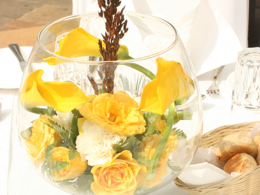 Yellow flower center piece in fish bowl.