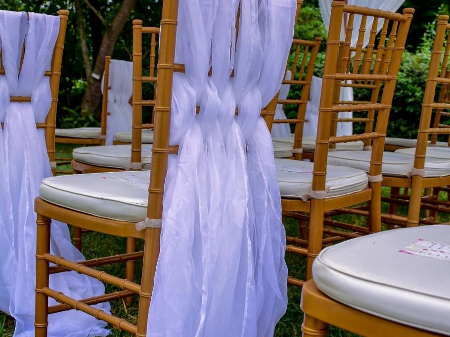 Gold chiavari chairs with white sheers.