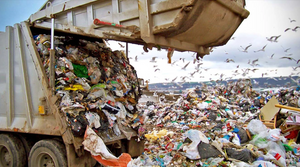 dump truck emptying rubbish into landfill