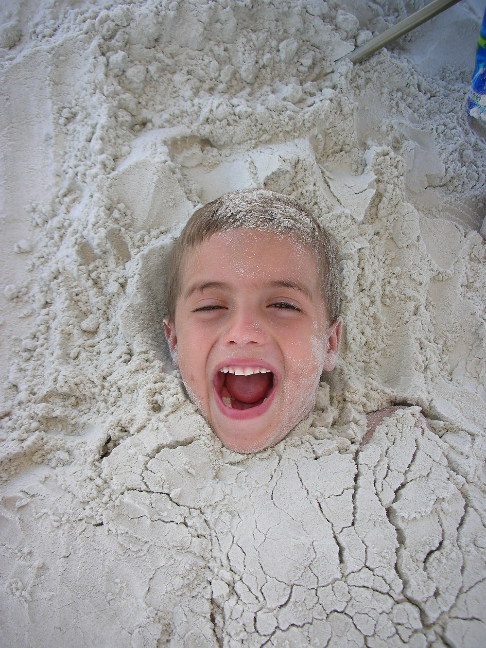 kid buried in sand