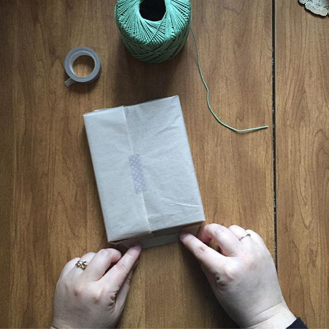 Photo of Kimberly's hands wrapping a box of cards in tissue paper with washi tape and cotton mint-colored string nearby.