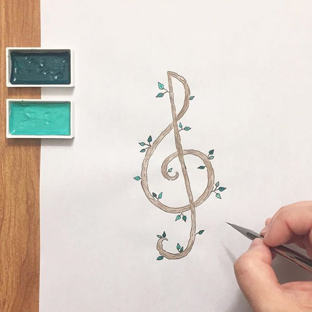 Kimberly's hand painting a wooden treble clef with leaves sprouting from it.