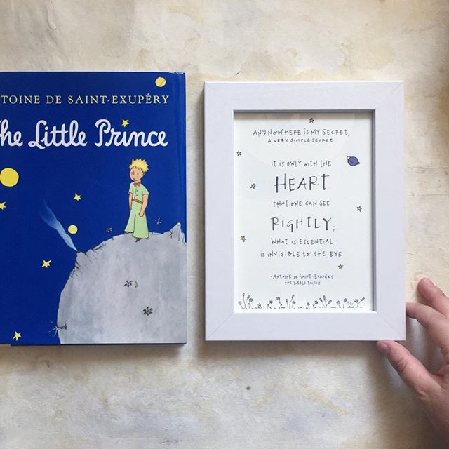 "Photo of ""The Little Prince"" book next to framed artwork featuring a quote from the book, ""And now here is my secret, a very simple secret. It is only with the heart that one can see rightly; what is essential is invisible to the eye."""