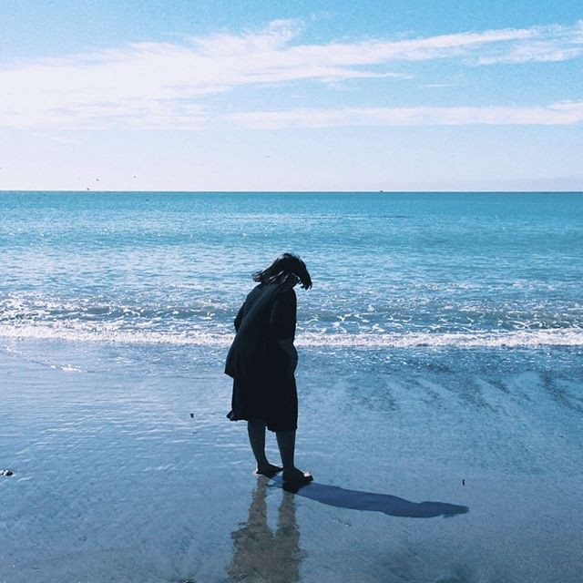 Photo of Kimberly standing on a beach looking away from the camera.