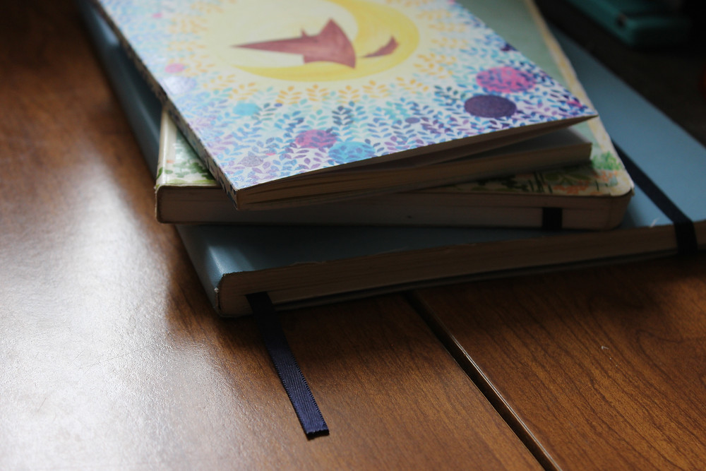 Photo: Stack of notebooks and journals on Kimberly's desk
