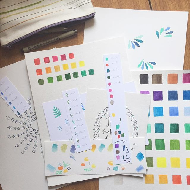 Image: Studio table covered with snippets of color studies and works in progress.