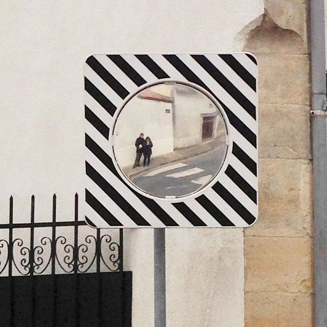 A reflection of Kimberly and her husband Jason in a mirrored street sign in Hermonville, France.