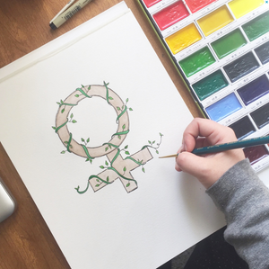 Photo of Kimberly's hand painting the women's sign with vines intertwined.