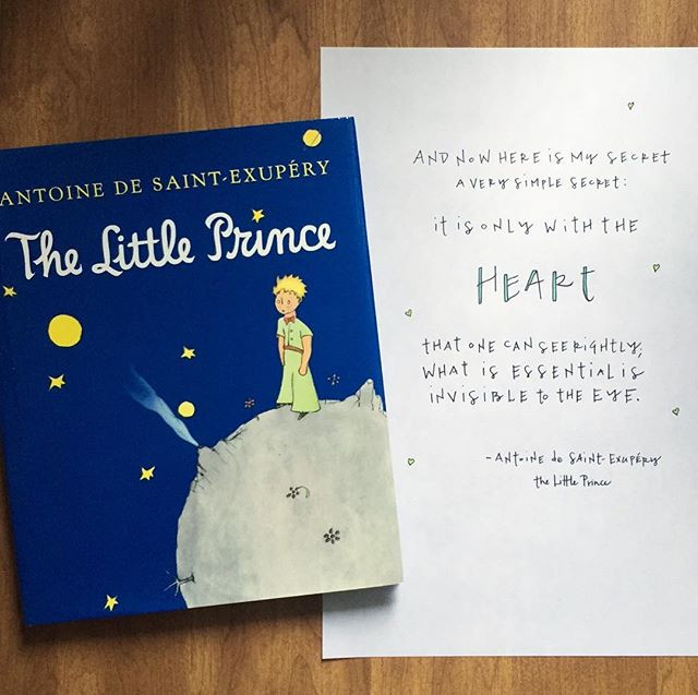 "Desk top view of a hand-lettered quote from ""The Little Prince"" by Antoine de Saint-Exupery"