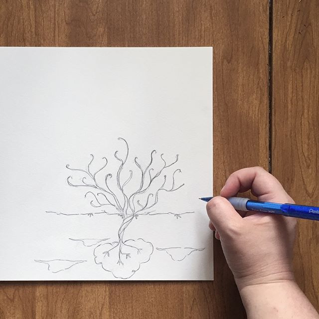 Kimberly sketching an upside-down tree with roots in the sky and leafy branches and clouds below the earth.