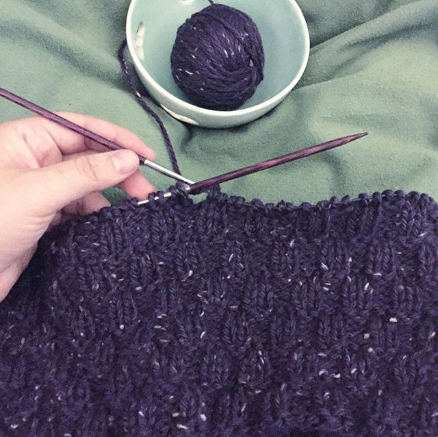 Photo of Kimberly's hand holding a knitting project–a cowl scarf of deep purple and grey-speckled yarn being knit on the round.