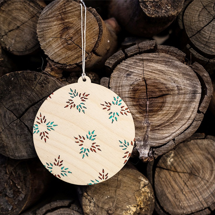 Hand-painted holiday ornament by Kimberly hanging from a wintry wood pile