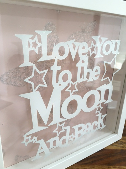 a beautiful frame available in white or black the quote i love you to the moon and back on the glass in vinyl and your choice of background paper